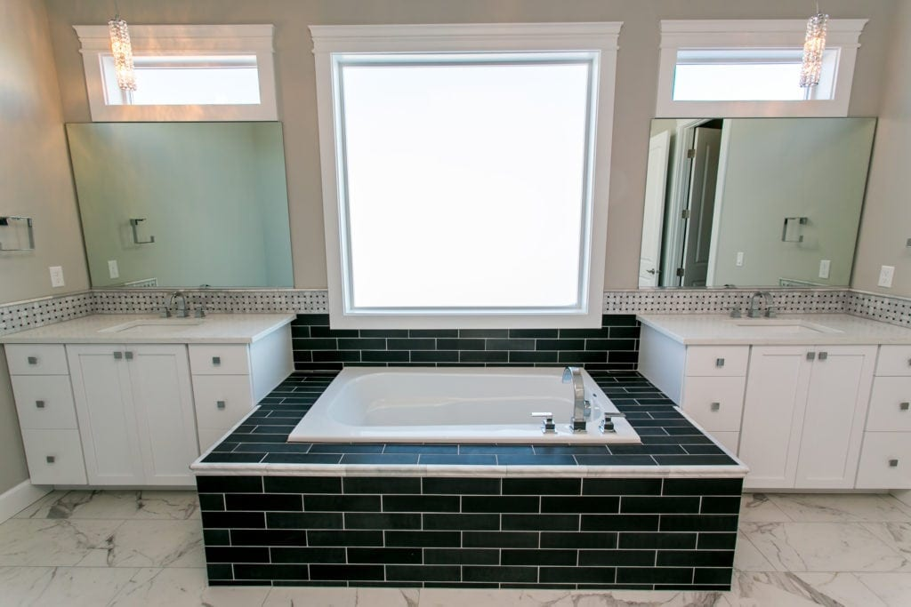 Black and white master bath with tiled tub deck. Built in Westcliffe neighborhood in Richland. Prodigy Homes, Inc. is building new construction homes in the Tri-Cities, Washington.