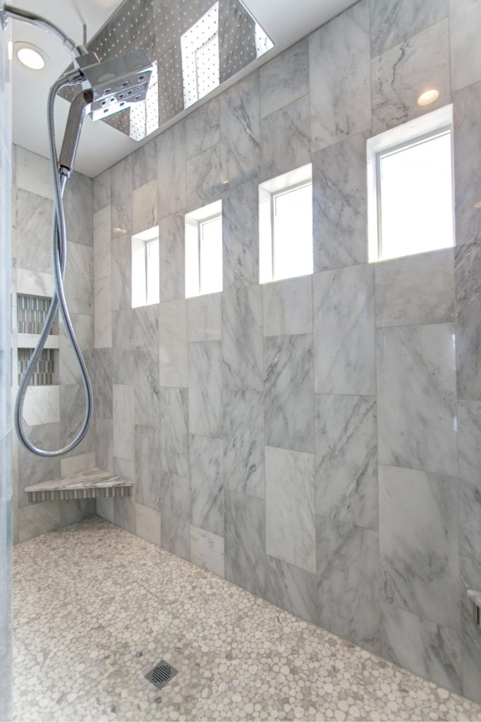 Master shower inspiration: marble shower with a giant rain head. Prodigy Homes is building new construction homes in Kennewick, Richland, West Richland, and Pasco, Washington.